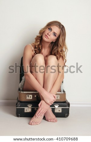 beautiful young woman is sitting on old leather suitcase. Beauty and Fashion girl.summer travel concept - stock photo