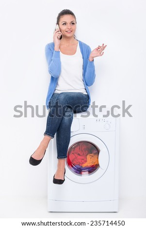 Beautiful young woman is sitting on the washing machine and speaking by phone. - stock photo