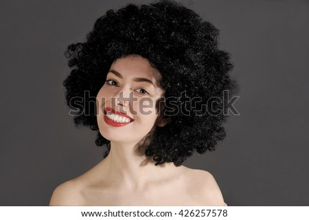 Beautiful young woman is smiling with a black curly wig on her head. Studio shot with dark background. - stock photo