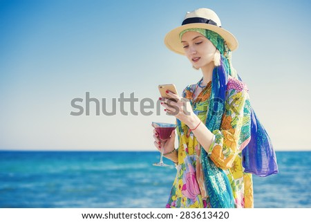 beautiful young woman is sms texting using an app on her smartphone, holding a martini cocktail on the beach - stock photo