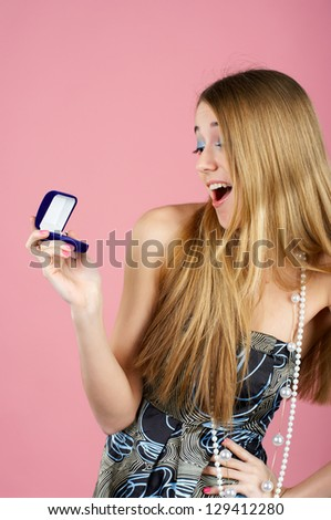 Beautiful young woman is surprised by an engagement ring in the opened gift box - stock photo
