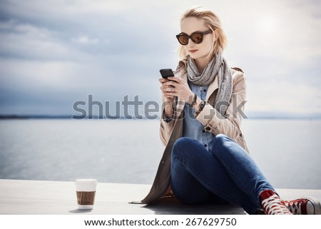 beautiful young woman is texting on her smartphone, while drinking a beverage by the sea - stock photo