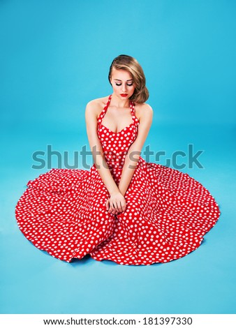 beautiful young woman isolated on blue in studio in old fashion clothes representing pinup and retro style