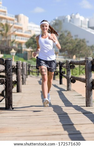 beautiful young woman jogging at the beach