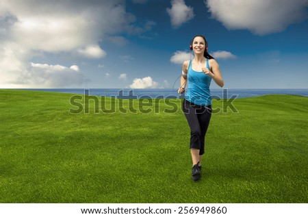Beautiful young woman jogging on a beautiful meadow while listen music - stock photo