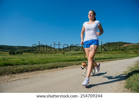 Beautiful young woman jogging with her pet (beagle dog) in nature - stock photo