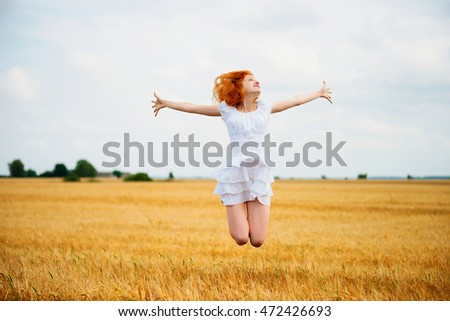 Beautiful young woman jumping at wheat field