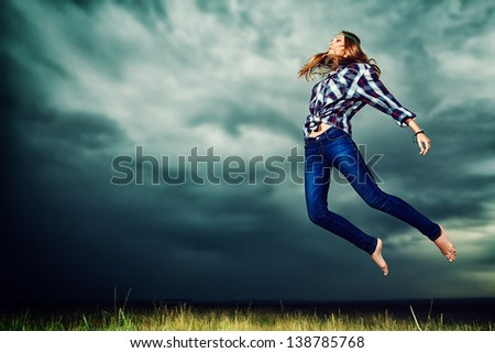 Beautiful young woman jumping in the field over stormy evening sky. - stock photo