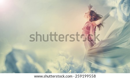 Beautiful young woman jumping on a giant flower - stock photo