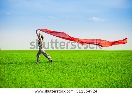 Beautiful young woman jumping on a green meadow with a colored red tissue. Happy female in wheat field with fabric. Summer picnic and freedom concept. - stock photo