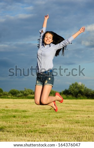 Beautiful young woman jumping on background of sky and clouds in the field