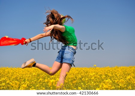 beautiful young woman jumping on field in summer