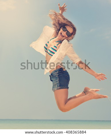 Beautiful young woman jumping on sea and sky background. Beach vacation, holiday, travel - stock photo