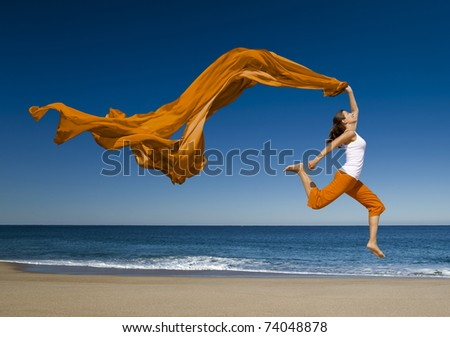 Beautiful young woman jumping on the beach with a colored tissue - stock photo