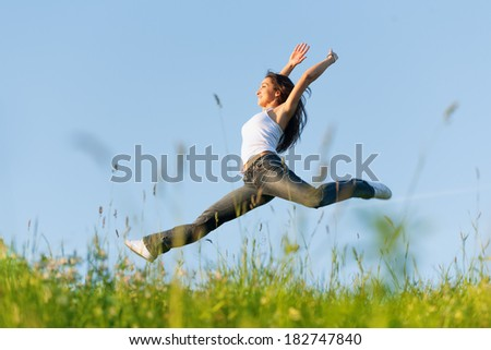 Beautiful young woman jumping on the green field  - stock photo