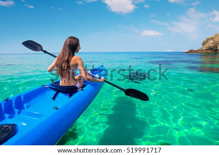 Beautiful young woman kayaking in the sea near the islands. Adventure by kayak.