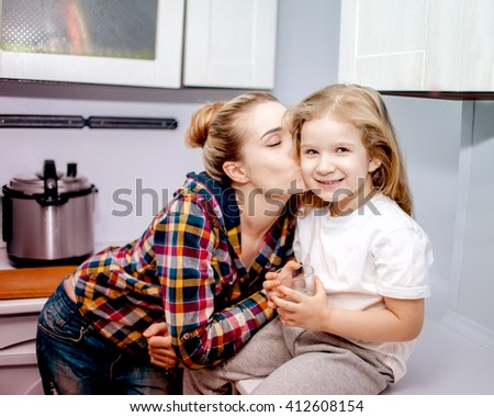 Beautiful young woman kiss child five years old at the kitchen - stock photo