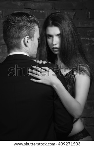 Beautiful young woman kissing her boyfriend and taking off his jacket while standing near brick wall in loft interior