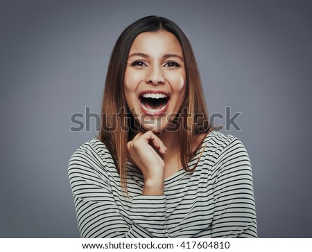 Beautiful young woman laghing out loud against a gray background - stock photo