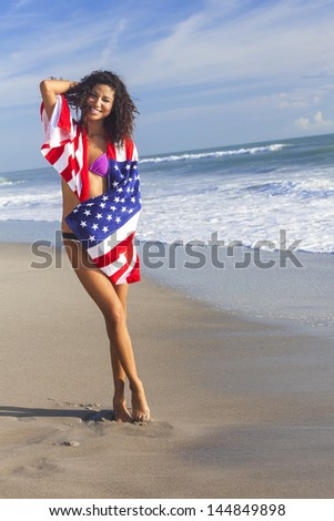 Beautiful young woman laughing wearing bikini and wrapped in American flag towel on a sunny beach - stock photo