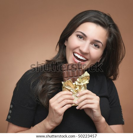 Beautiful young woman laughing with chocolate bar - stock photo