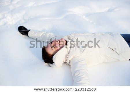 Beautiful young woman laying down on a snow and making angel figure - stock photo