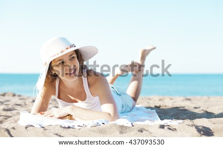 Beautiful young woman laying on the beach
