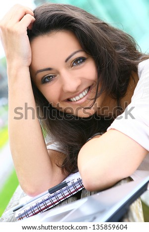 Beautiful young woman learning outdoors at sunny day