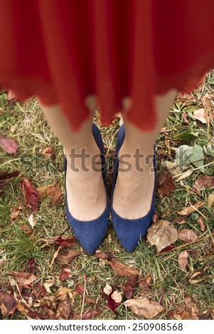 Beautiful young woman legs in red dress with blue high heel shoes, up view - stock photo