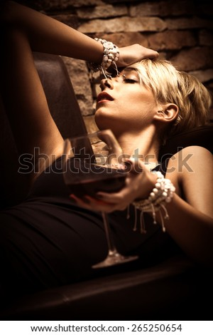 beautiful young woman lie holding glass of red wine in hand, side view, close up, indoor shot - stock photo