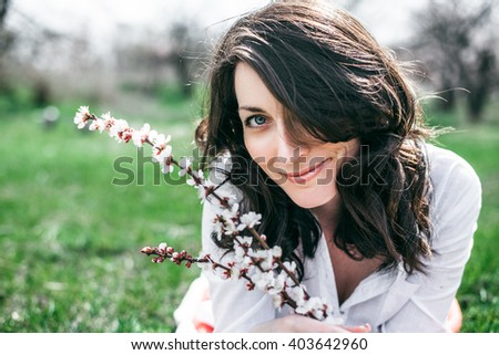 Beautiful young woman lies on green grass in summer green city park. - stock photo
