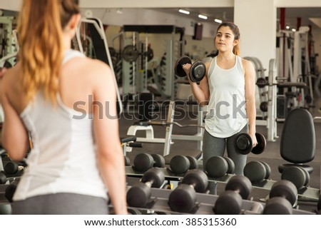 Beautiful young woman lifting a couple of dumbbells in front of a mirror at the gym