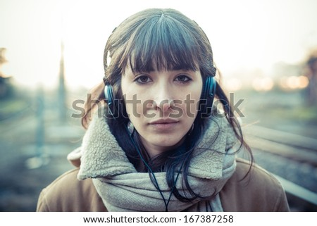 beautiful young woman listening to music headphones  in the city winter