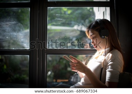 Beautiful young woman listening to music in headphones and phone on windows background.