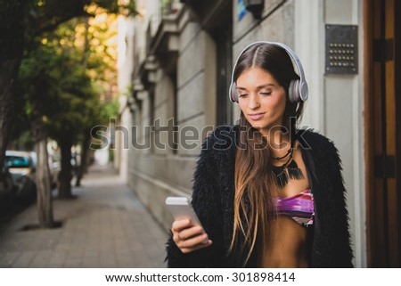 Beautiful young woman listening to music in the city and wearing modern wireless head phones. - stock photo