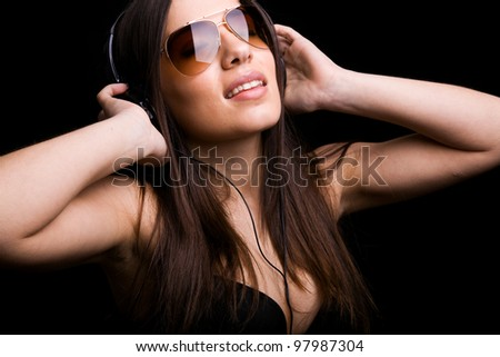 Beautiful young woman listening to music with headphones on black background - stock photo