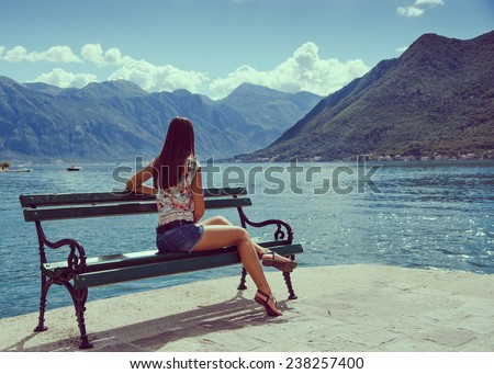 Beautiful young woman looking and waiting at the seacoast. Sunny day. Montenegro, Europe. Retro style toning image. - stock photo