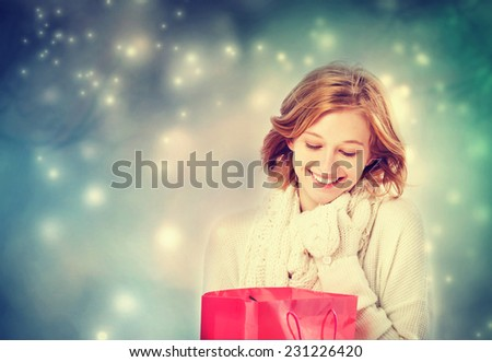 Beautiful young woman looking at a gift bag in snowy night - stock photo