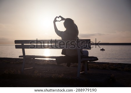 Beautiful young woman looking at amazing sunrise, showing heart symbol. Summer photo. - stock photo