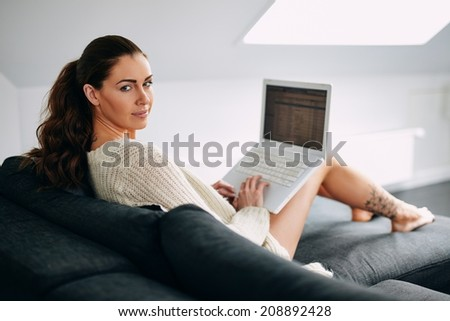 Beautiful young woman looking at camera while using laptop on sofa. Caucasian female model working on laptop on couch at home. - stock photo