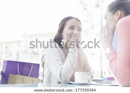Beautiful young woman looking at friend sharing secrets at outdoor cafe - stock photo