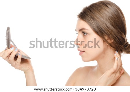 Beautiful young woman looking at herself in a hand mirror - stock photo