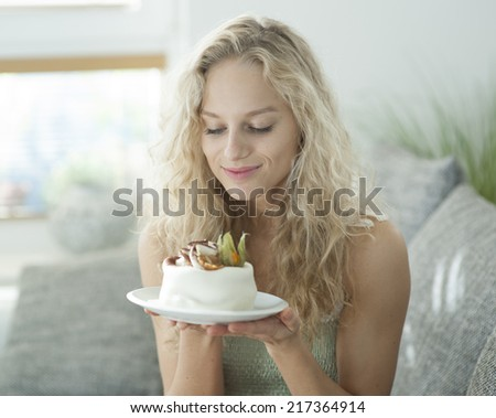 Beautiful young woman looking at tempting cake in house - stock photo