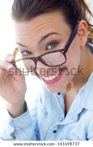 beautiful young woman looking at the camera with his glasses