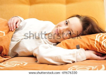 Beautiful young woman looking attractive smiling - indoors at her bedroom lifestyle - stock photo