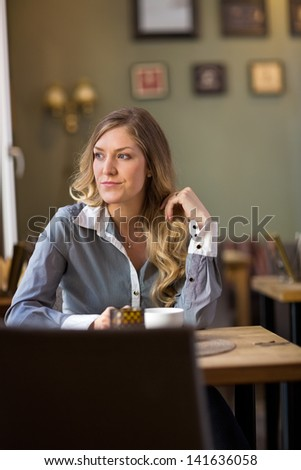Beautiful young woman looking away at cafe - stock photo
