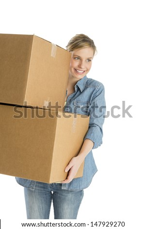 Beautiful young woman looking away while carrying stacked cardboard boxes against white background