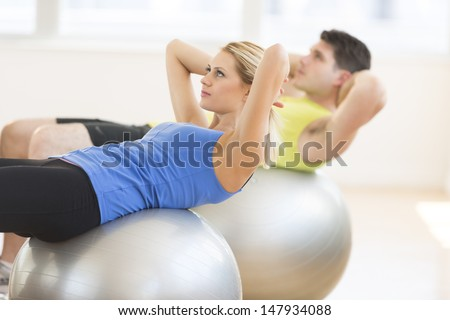 Beautiful young woman looking away while exercising on fitness ball with man in background at gym - stock photo