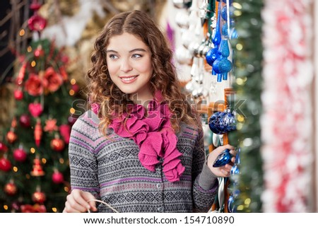 Beautiful young woman looking away while shopping at Christmas store