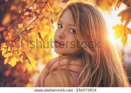 Beautiful young woman looking back in to the camera, sunset in the background and autumn colored leafs - stock photo